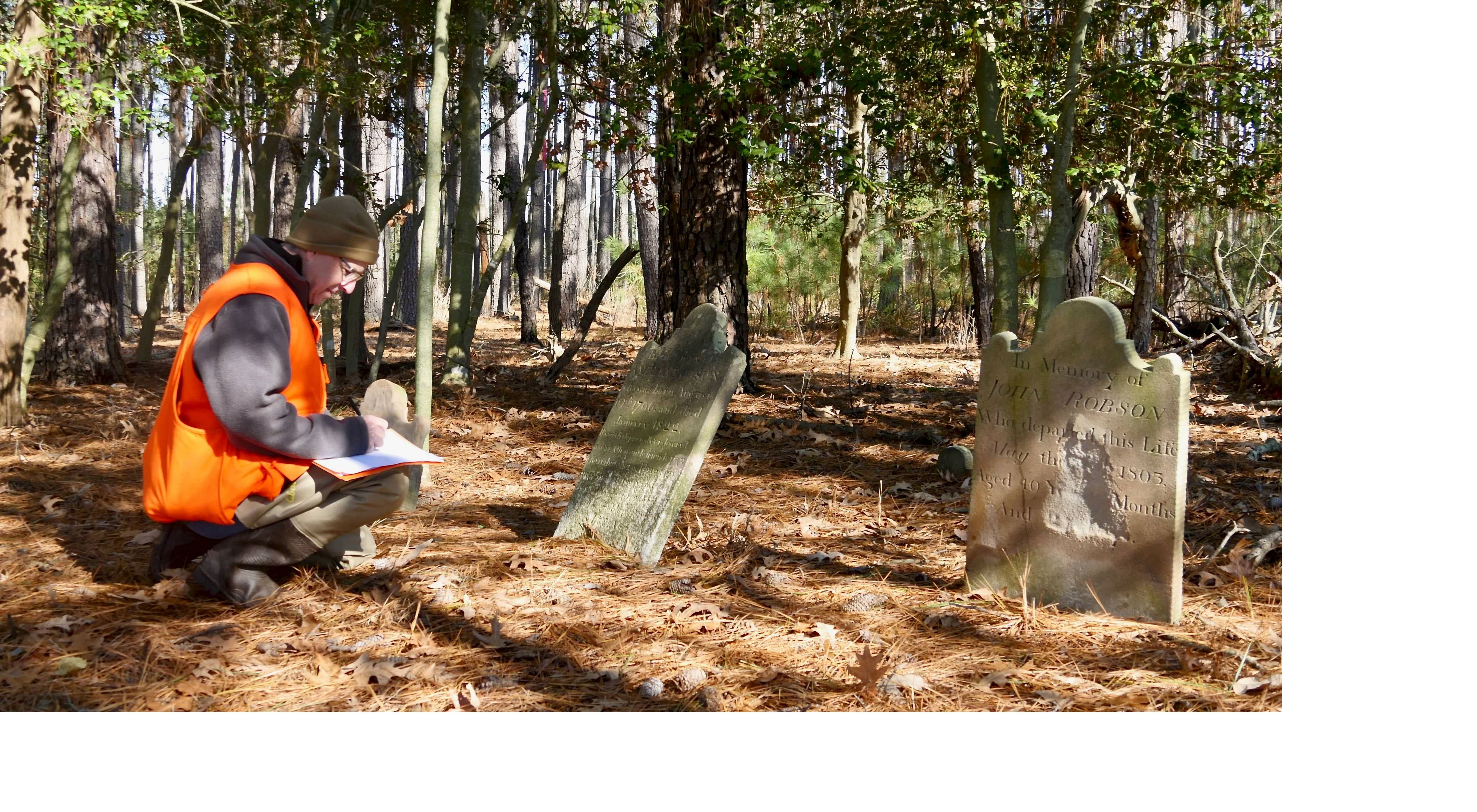 man kneels with pen and paper in front of old tombstone in wooded area