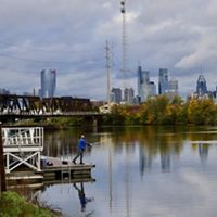 The Philadelphia city skyline is reflected in the wide flat water of the Delaware River as a man casts a fishing line from a short dock along the river's edge.