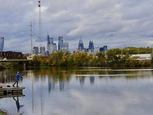 A man stands on a short dock casting a line into the river. Clouds hang low over the Philadelphia city skyline in the background.