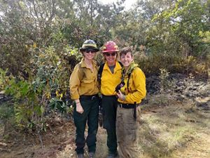 Three smiling women wearing yellow fire gear pose shoulder to shoulder during a controlled burn. A wide band of burned vegetation on the ground behind them marks out the burn unit at the edge of a for