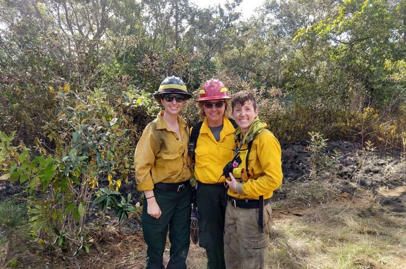 Three smiling women wearing yellow fire gear pose shoulder to shoulder during a controlled burn. A wide band of burned vegetation on the ground behind them marks out the burn unit.