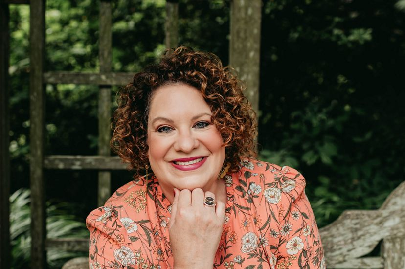 Professional headshot PA/DE Executive Director Lori Brennan. A smiling woman rests her chin on right hand. She is wearing a peach blouse with floral design, standing in front of a rustic backdrop.