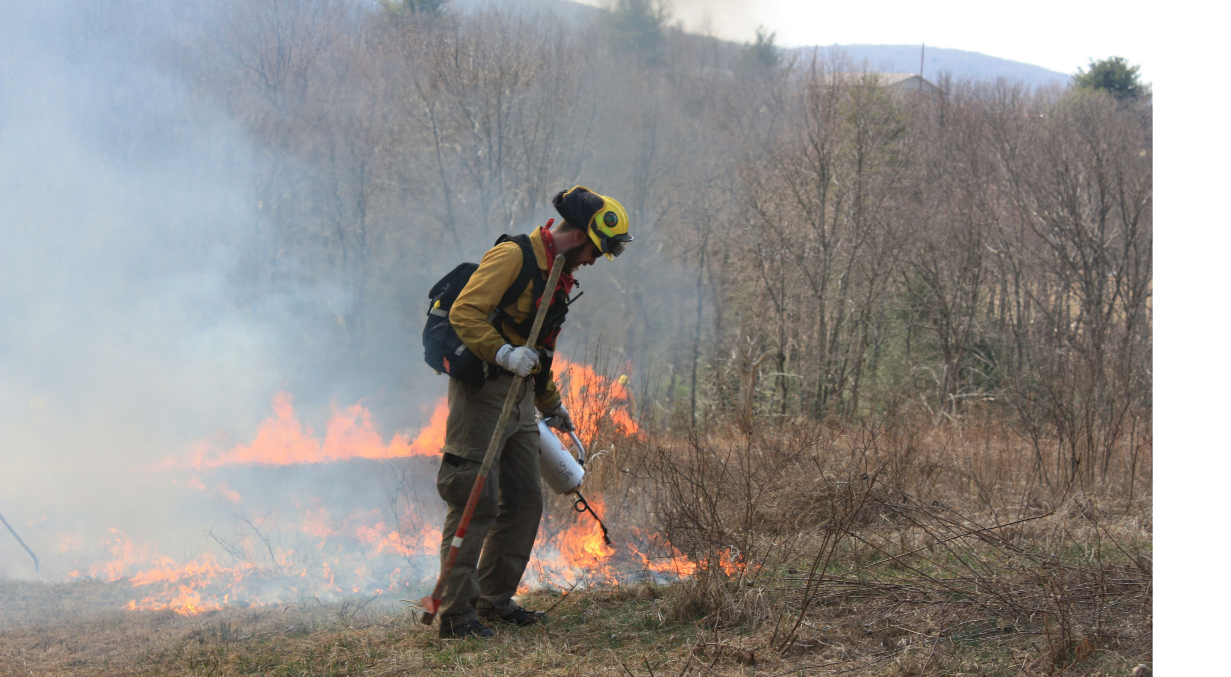 A burn crew dressed in yellow directs fire towards the ground.