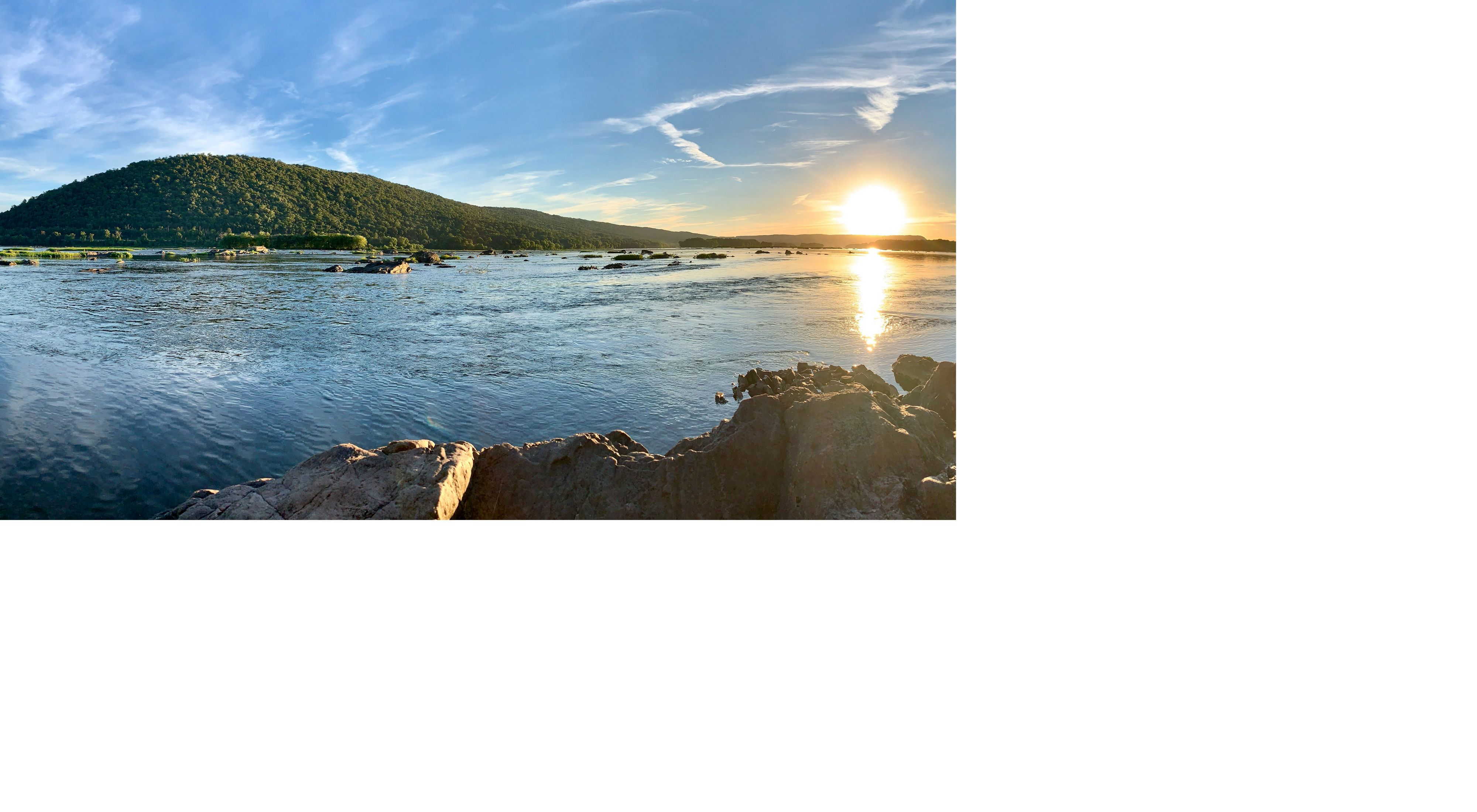 View of Cove Mountain across the Susquehannah River. The rising sun is reflected in the water as the river eddys and pools around the large rocks at its edges and middle.