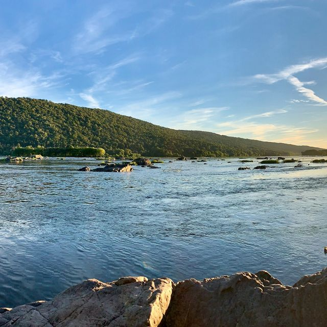 Sunrise over the Susquehanna River. The sun is reflected in the still water to the right of a tall, forested mountain ridge. Rocky outcroppings run along the river's shore in the foreground.
