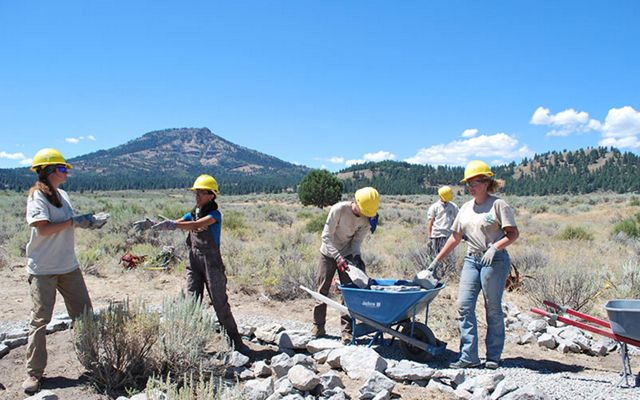 A team of people in hard hats laying rocks along an arid trail.