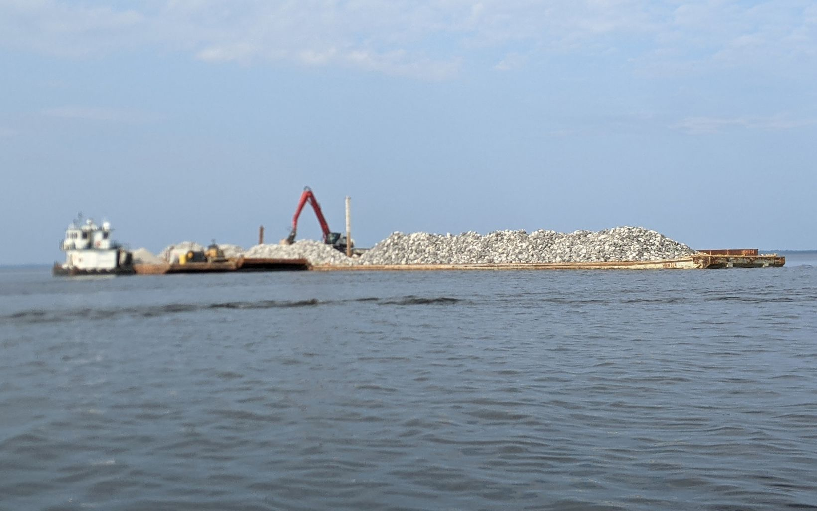 Barge containing limestone rock with an excavator in the bay.
