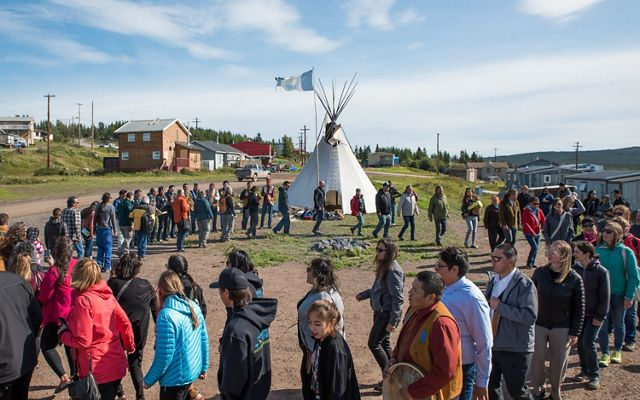 Men women and children of lutsel ke first nation dance in a circle near a tipi in a first nations native american community