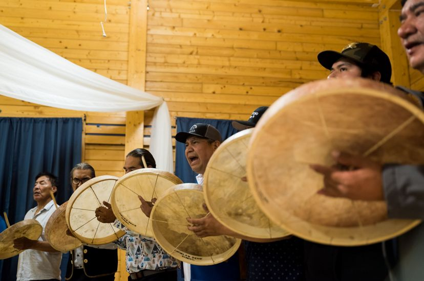 first nation native american men beating drums during a ceremony
