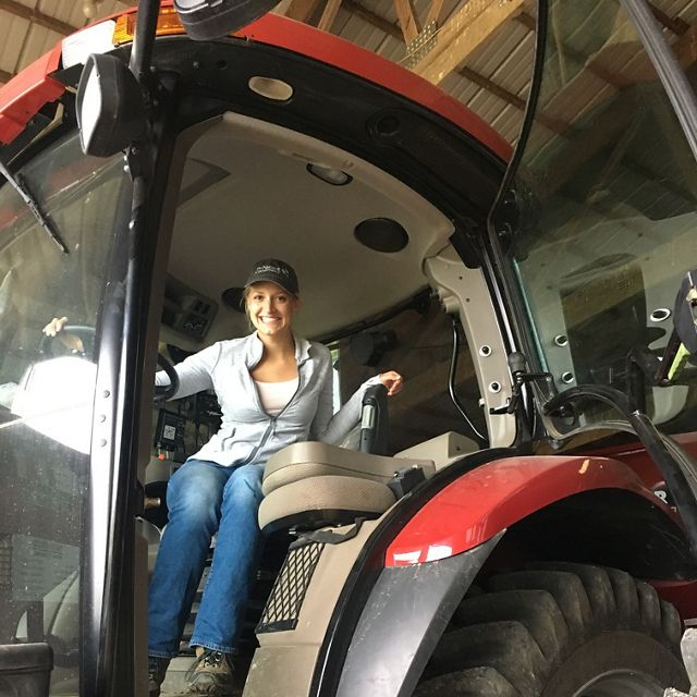 Our fellow Paige sits in the driver's seat of a large tractor.