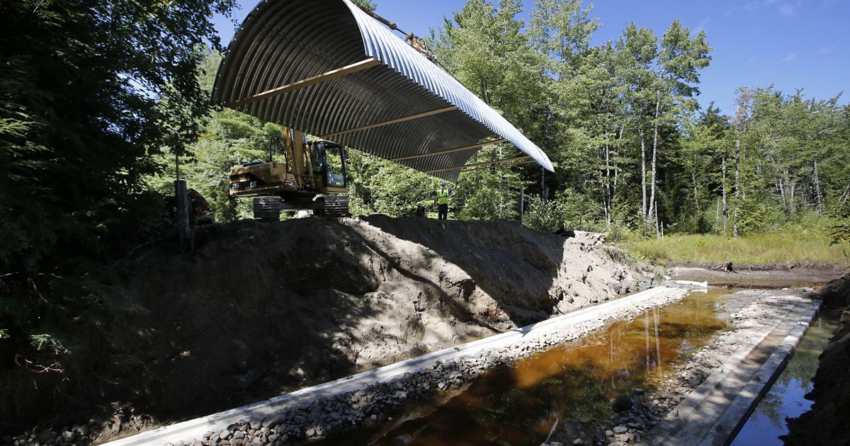 Open-bottom culvert is lowered into place