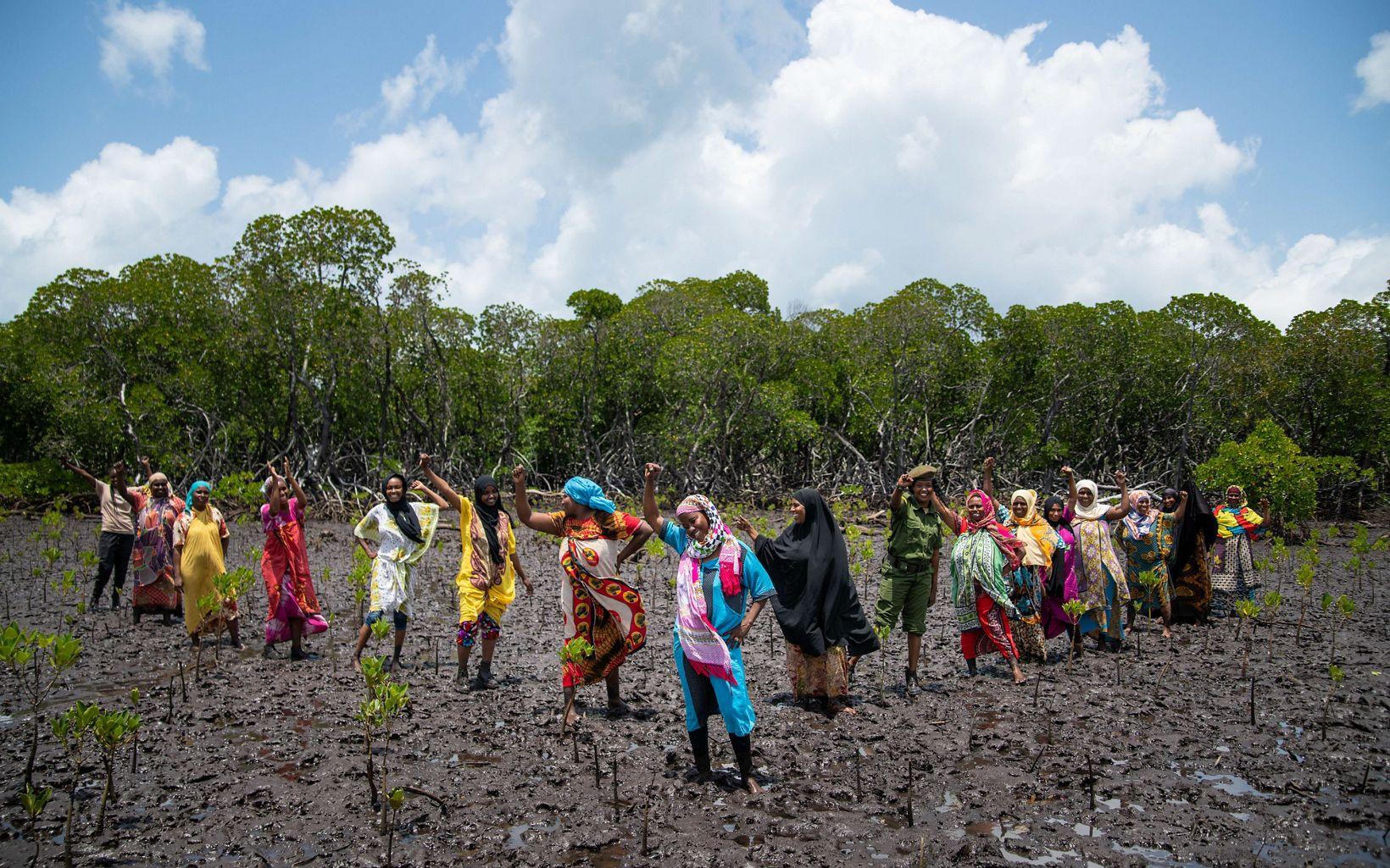 women standing in mud