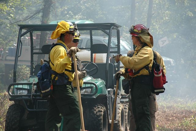 Two members of a fire crew talk to each other.