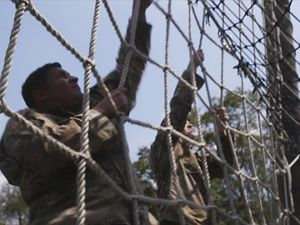 Soldiers climb on ropes.