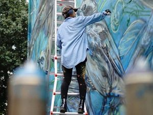 An artist stands on a ladder to paint a mural on a wall.