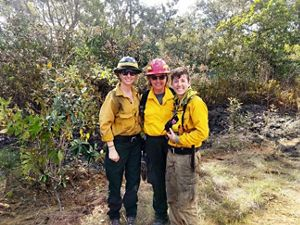 Three women pose in helmets and yellow shirts.