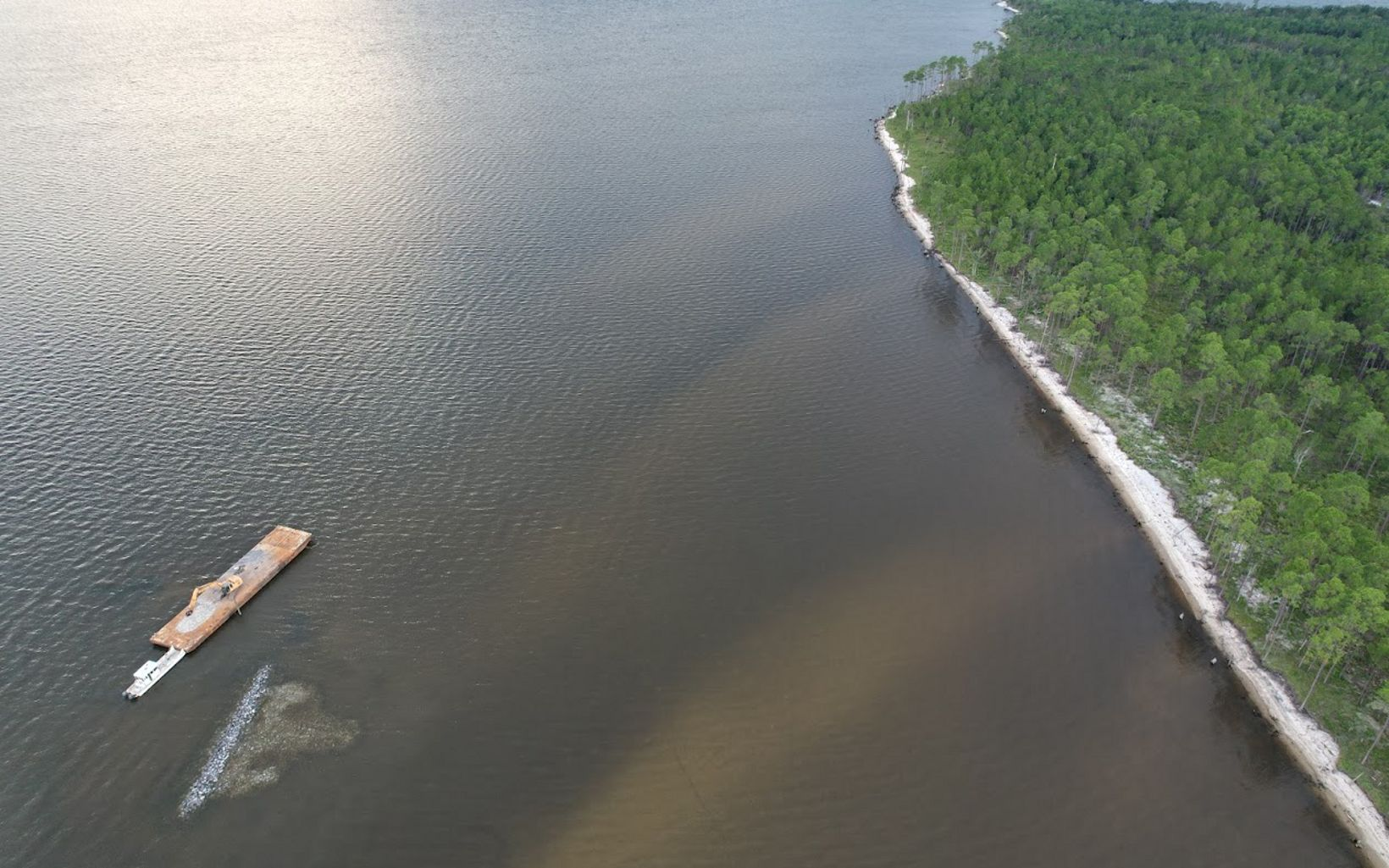 Aerial view of barge with nearly-completed oyster reef under construction.