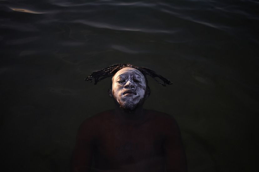 A young African refugee from the Democratic Republic of Congo floating in the waters of Guanabara Bay, Ramos Beach.