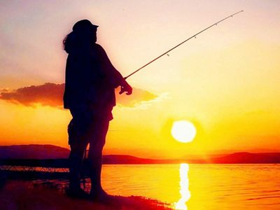 A person fishing in the sunset.