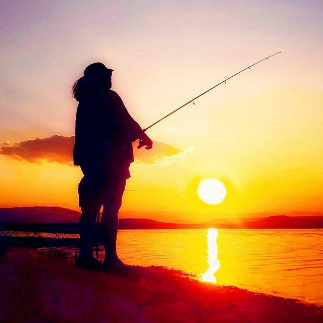 A person fishing as the sun sets in Wyoming.