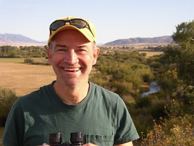A man in a green shirt and hat smiling.