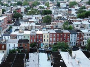 An aerial view of row house rooftops in an urban area.