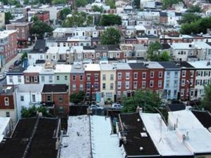 An urban landscape of rooftops and row houses.