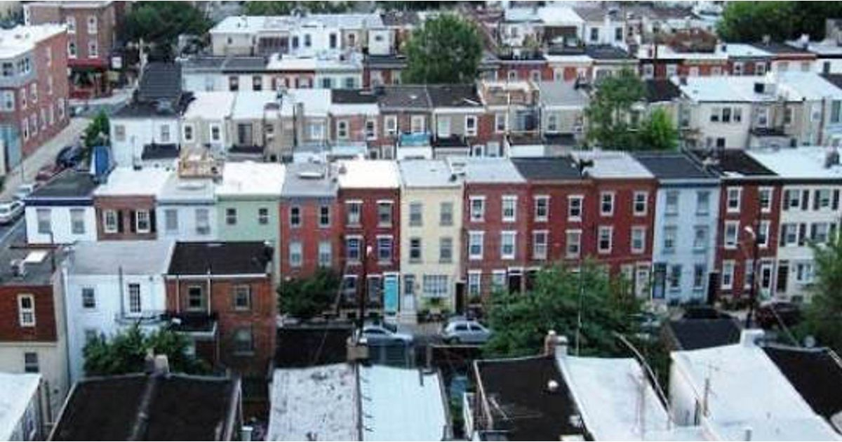 An aerial view of row house rooftops in an urban area