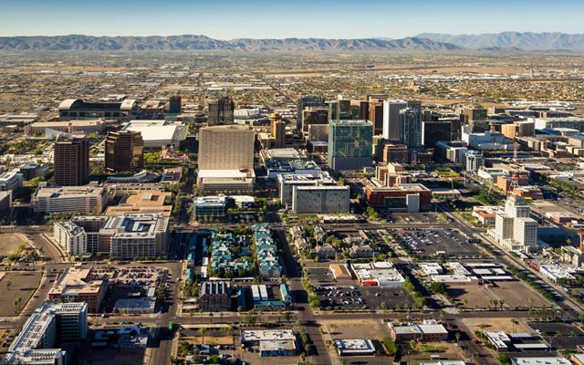 Aerial view of Phoenix with skyscrapers, parking lots and mountains in the distance.
