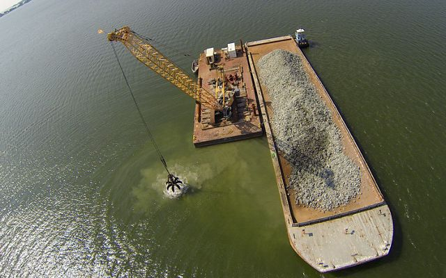 Aerial drone view of barge depositing granite substrate for oyster reefs in the Piankatank River.