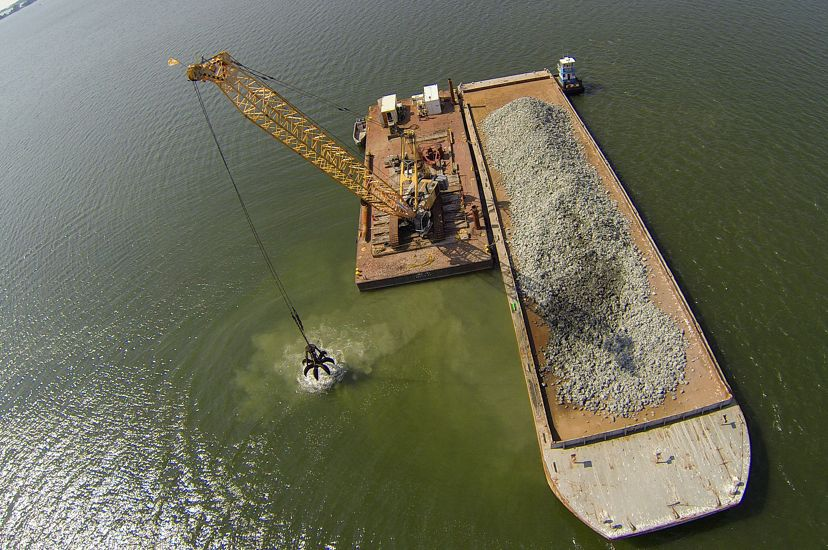 Aerial view looking down on a floating barge carrying crushed blocks of concrete. The grabber claw of a crane floating next to the barge dumps a load of concrete into the water.