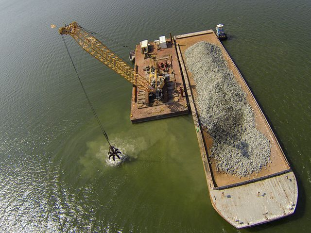 Aerial view looking down onto a floating barge depositing crushed granite at the site of a new oyster reef.