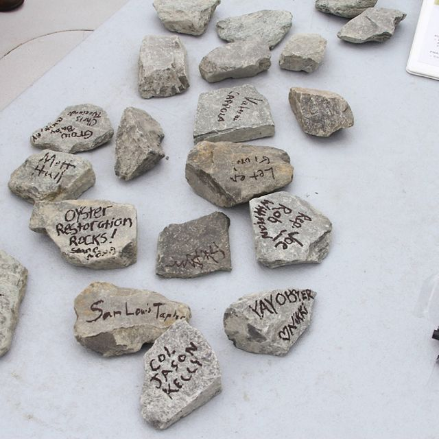 Small pieces of granite rock sit spread out on a table. Each piece of rock is signed with a message from people participating in an oyster reef dedication ceremony.