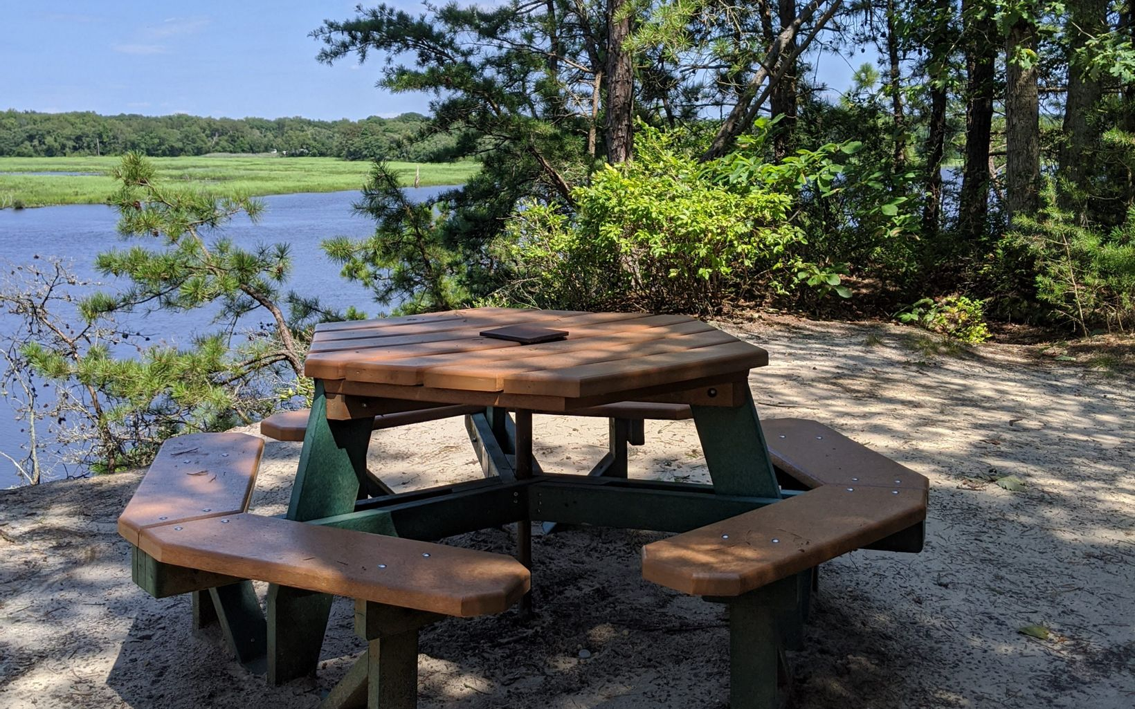 A picnic table sits next to a river and wetlands.