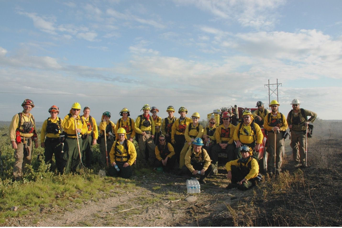 Two dozen people wearing yellow fire gear pose together in a group in an open field at the end of a controlled burn.