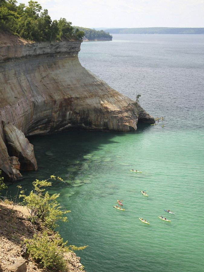 A group of 5 kayakers in green waters next to a cliff.