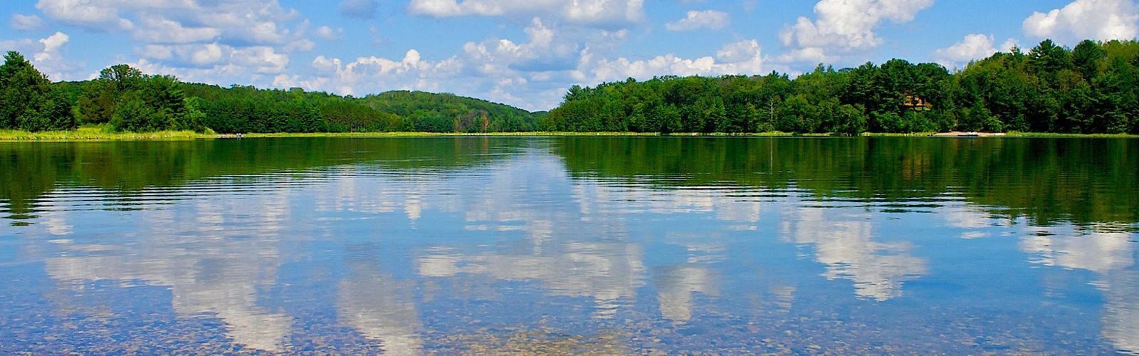 White clouds and blue sky reflected in a tree-lined lake.