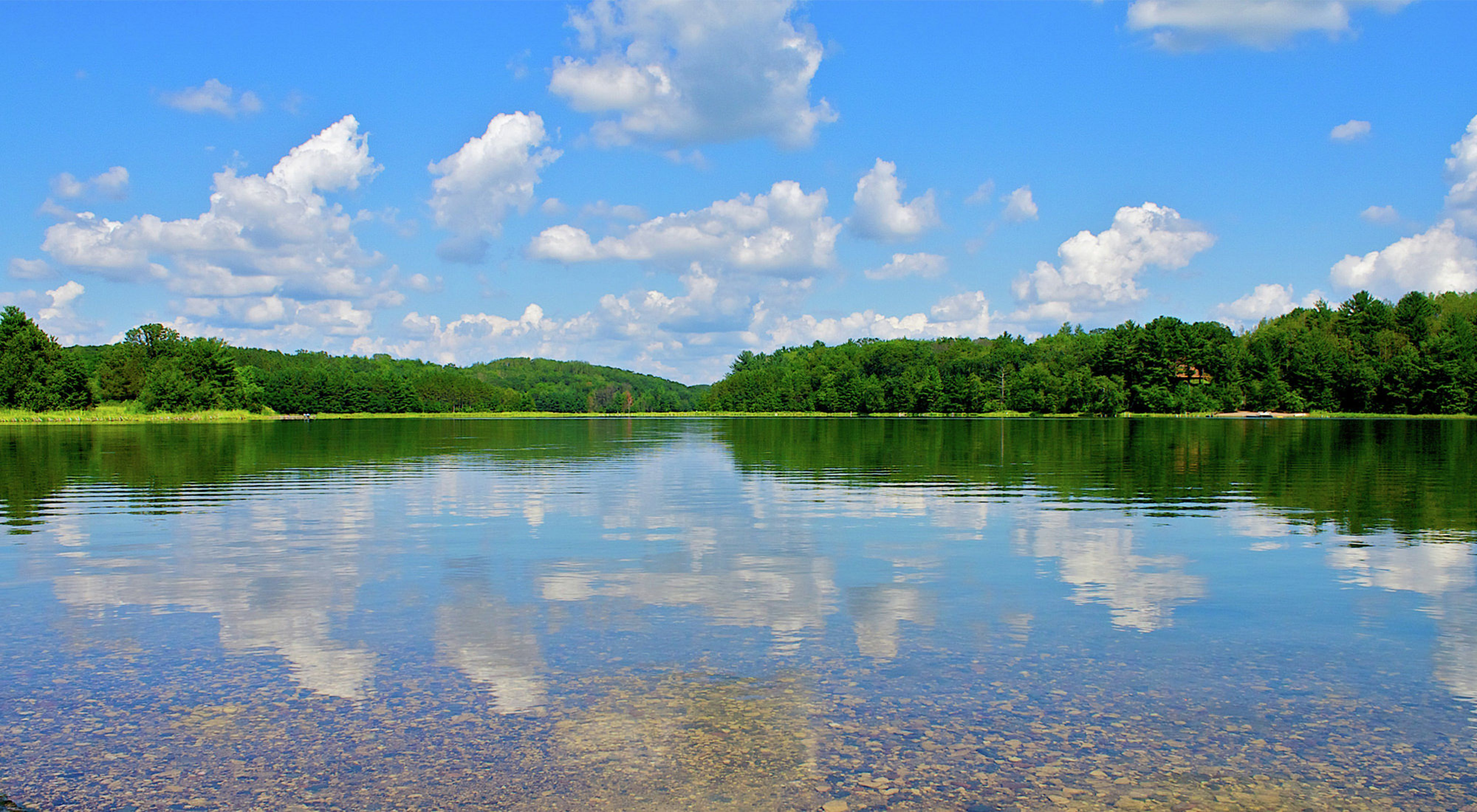 Clouds in a blue sky reflect in a forest lined lake.