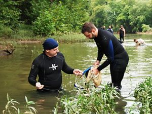 Two men in wet suit study a river.