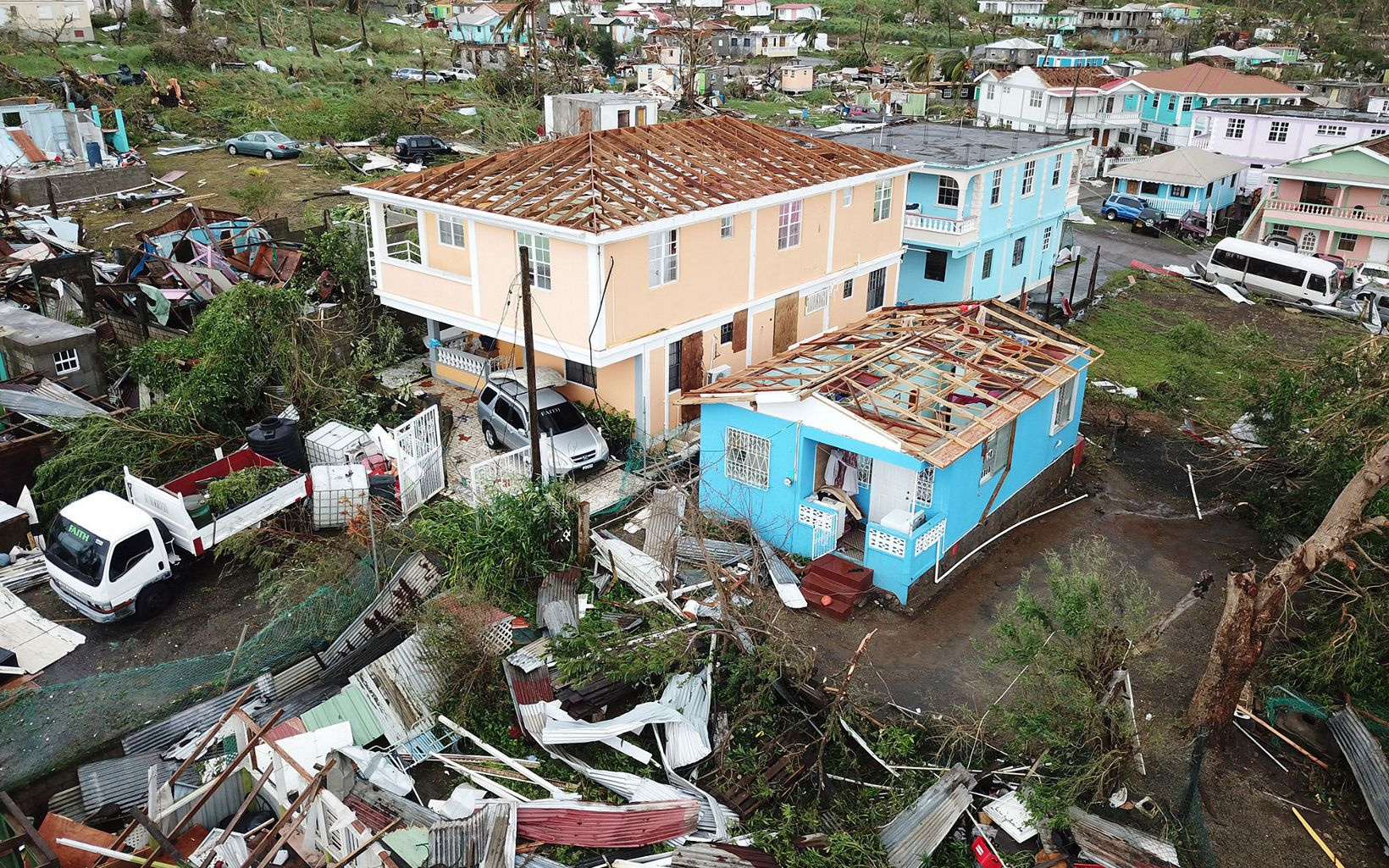 Houses missing roofs in Dominica after Hurricane Maria