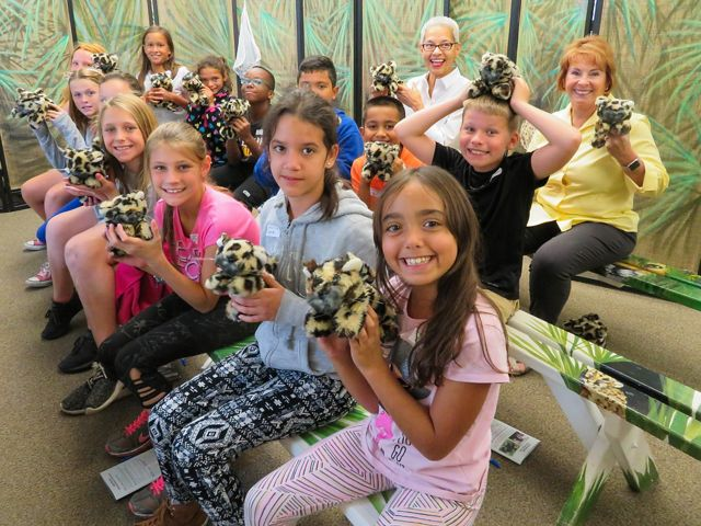 Elementary students smile in a classroom with teachers and chaperones as they hold stuffed animals of baby florida panthers