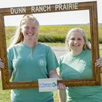 Visitors taking a photo in a wooden frame at the Dunn Ranch Prairie Visitor's Center in Missouri.