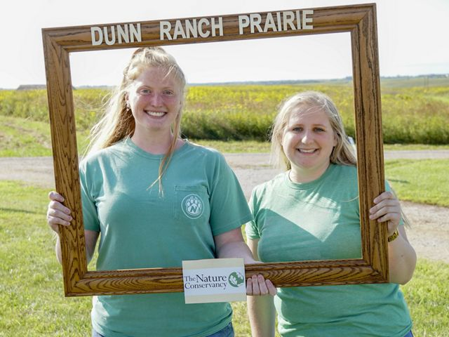 Two women smile and pose while holding up a wooden frame labeled 'Dunn Ranch Prairie.'