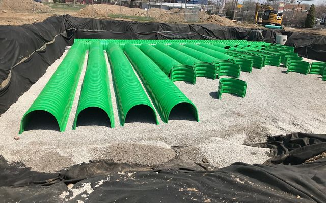 Green underground cistern tubes being layed out in a grid.