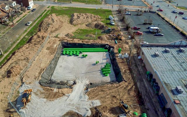 An aerial view of construction site with green cistern tubes being installed on an open lot.