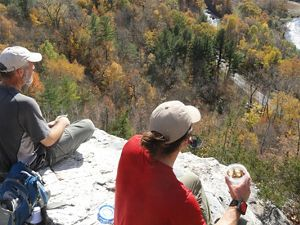 Two people atop a cliff looking over bright fall foliage.
