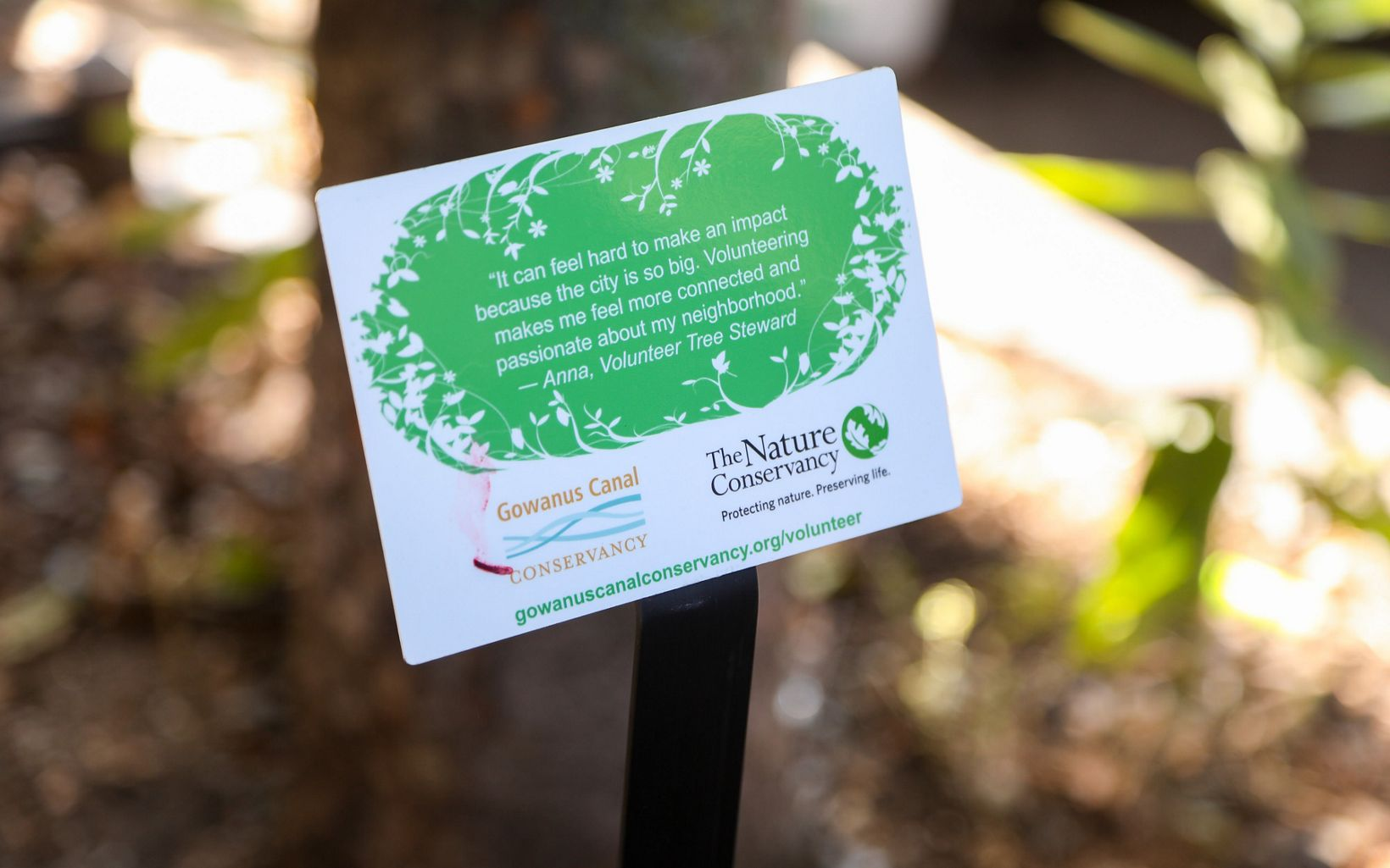 A closeup of a sign with a volunteer tree steward quote with the logos of The Nature Conservancy and Gowanus Canal Conservancy in view.