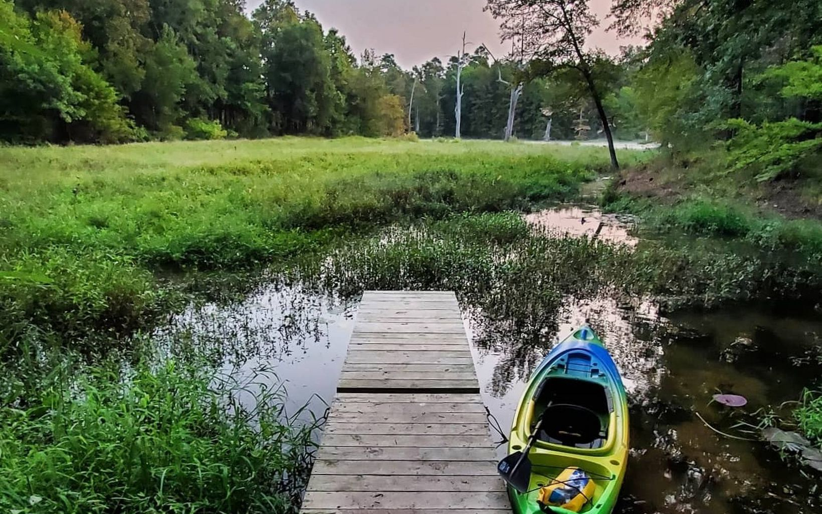 A kayak next to a small wooden dock.