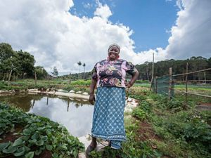 A farmer stands in front of her rainwater harvesting pan