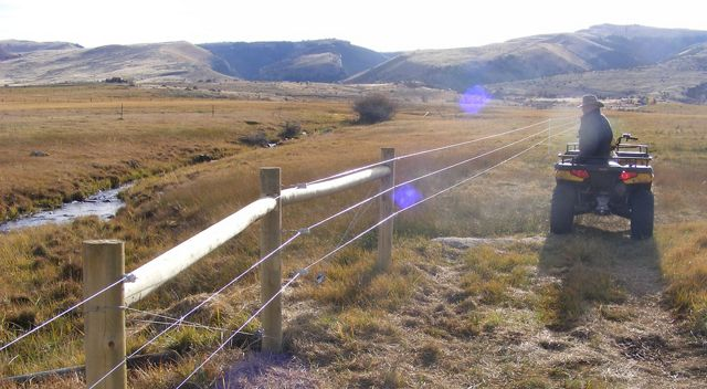 A rancher on an ATV surveys his wildlife friendly fence.